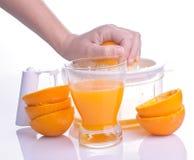 Mano que exprime la naranja para el jugo Imagen de archivo libre de regalías