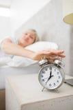 Mano que extiende de la mujer al despertador en cama Fotos de archivo libres de regalías