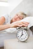 Mano que extiende de la mujer al despertador en cama Fotos de archivo