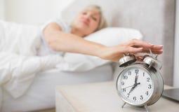 Mano que extiende de la mujer al despertador en cama Foto de archivo libre de regalías