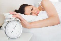 Mano que extiende de la mujer al despertador en cama Foto de archivo