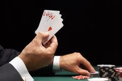 Mano que gana del jugador de póker del rubor real de las tarjetas foto de archivo libre de regalías