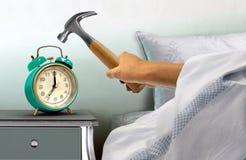 Mano que golpea el despertador con el martillo Fotografía de archivo
