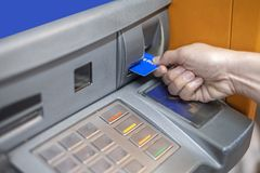 Mano que inserta tarjeta de cajero automático en la máquina del banco del cajero automático para retirar el dinero fotografía de archivo libre de regalías