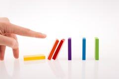 Mano que juega con dominó coloreado Imagen de archivo