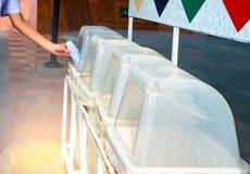 Mano que lanza la botella plástica vacía en la papelera de reciclaje Disposición de la basura reciclable y reutilizable fotos de archivo
