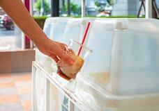 Mano que lanza la taza de café plástica vacía en la papelera de reciclaje imágenes de archivo libres de regalías