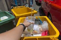 Mano que lanza la taza plástica en botes de basura Imagenes de archivo