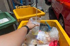 Mano que lanza la taza plástica en botes de basura Foto de archivo
