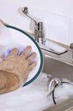 Mano que lava los platos Imagen de archivo libre de regalías