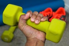 Mano que levanta pesa de gimnasia verde clara Imagenes de archivo