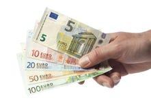 Mano que lleva a cabo cuentas de moneda europeas imagen de archivo