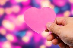 Mano que lleva a cabo día de tarjetas del día de San Valentín de los corazones de la etiqueta Imagen de archivo libre de regalías