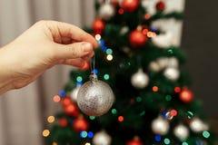 Mano que lleva a cabo el cierre de plata del ornamento de la bola para arriba que adorna la Navidad Imágenes de archivo libres de regalías