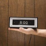 Mano que lleva a cabo el conjunto retro del reloj Fotografía de archivo libre de regalías