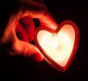 Mano que lleva a cabo el corazón ardiente de la vela Fotografía de archivo libre de regalías