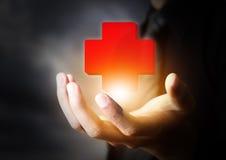 Mano que lleva a cabo el icono de los primeros auxilios Fotografía de archivo libre de regalías