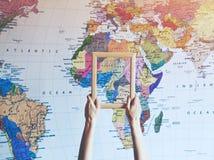 Mano que lleva a cabo el marco de madera vacío en el mapa de África fotos de archivo libres de regalías