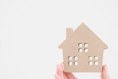 Mano que lleva a cabo el modelo miniatura de la casa Foto de archivo libre de regalías