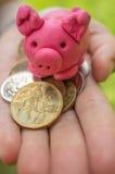 Mano que lleva a cabo el moneybox - guarro rosado como símbolo de ahorros foto de archivo