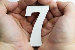 Mano que lleva a cabo el número siete Imágenes de archivo libres de regalías