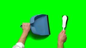 Mano que lleva a cabo el recogedor de polvo y barrer almacen de video