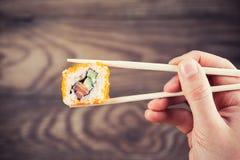 Mano que lleva a cabo el rollo de sushi usando los palillos Imágenes de archivo libres de regalías