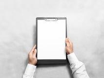 Mano que lleva a cabo el tablero de clip en blanco con la maqueta del diseño del Libro Blanco Fotos de archivo libres de regalías