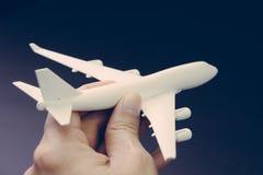 Mano que lleva a cabo el vuelo limpio blanco del aeroplano o de los aviones del juguete en fondo negro oscuro usando como viaje y imagen de archivo