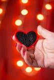 Mano que lleva a cabo forma del corazón en fondo rojo Foto de archivo