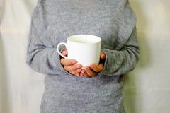 Mano que lleva a cabo la bebida caliente con el suéter gris Fotos de archivo libres de regalías