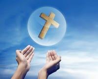 Mano que lleva a cabo la cruz cristiana en esfera Fotos de archivo