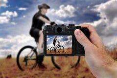 Mano que lleva a cabo la fotografía de la cámara de Biking de la montaña Fotos de archivo