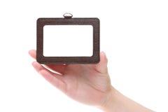 Mano que lleva a cabo la insignia en blanco de la identificación Imagen de archivo libre de regalías