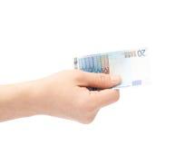Mano que lleva a cabo la nota del euro veinte aislada Imagenes de archivo