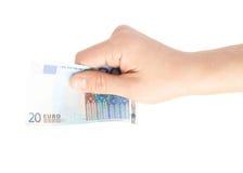 Mano que lleva a cabo la nota del euro veinte aislada Fotos de archivo