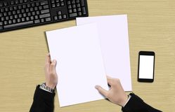 Mano que lleva a cabo la opinión superior del papel en blanco Imagen de archivo