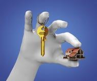 Mano que lleva a cabo la pequeña casa y algunos claves Foto de archivo