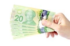 Mano que lleva a cabo los billetes de dólar #1 del canadiense veinte Imagenes de archivo