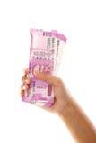 Mano que lleva a cabo 2000 notas de la rupia contra blanco Fotos de archivo libres de regalías