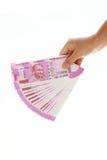 Mano que lleva a cabo 2000 notas de la rupia contra blanco Imágenes de archivo libres de regalías