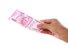 Mano que lleva a cabo 2000 notas de la rupia contra blanco Foto de archivo libre de regalías