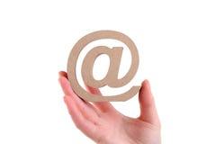 Mano que lleva a cabo símbolo de madera del correo electrónico Fotografía de archivo libre de regalías