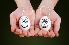 mano que lleva a cabo sostener los huevos con las caras sonrientes Fotografía de archivo libre de regalías