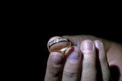 Mano que lleva a cabo un anillo con el fondo negro Foto de archivo libre de regalías