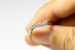 Mano que lleva a cabo un anillo de diamante foto de archivo