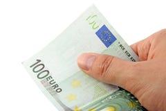 Mano que lleva a cabo una cuenta del euro 100 Imágenes de archivo libres de regalías