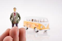 Mano que lleva a cabo una figura cerca de una furgoneta Foto de archivo libre de regalías
