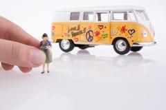 Mano que lleva a cabo una figura cerca de una furgoneta Fotografía de archivo libre de regalías