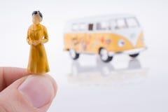 Mano que lleva a cabo una figura cerca de una furgoneta Imagen de archivo libre de regalías
